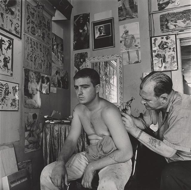 "Danny Lyon, ""Bill Sanders, Tattoo Artist, Houston, Texas,"" 1968. Gelatin silver print, Image: 20.7 x 20.7 cm (8 3/16 x 8 3/16 in.); sheet: 35.6 x 27.9 cm (14 x 11 in.). Collection of the artist, L170 © Danny Lyon, courtesy Edwynn Houk Gallery, New York"